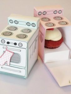 Miniature paper ovens filled with cupcake