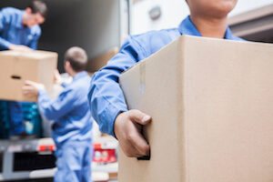 Men unloading boxes from moving truck