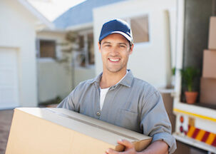 Mover man taking box out of back of truck and smiling