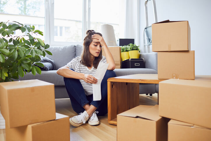 Worried woman among her moving boxes.