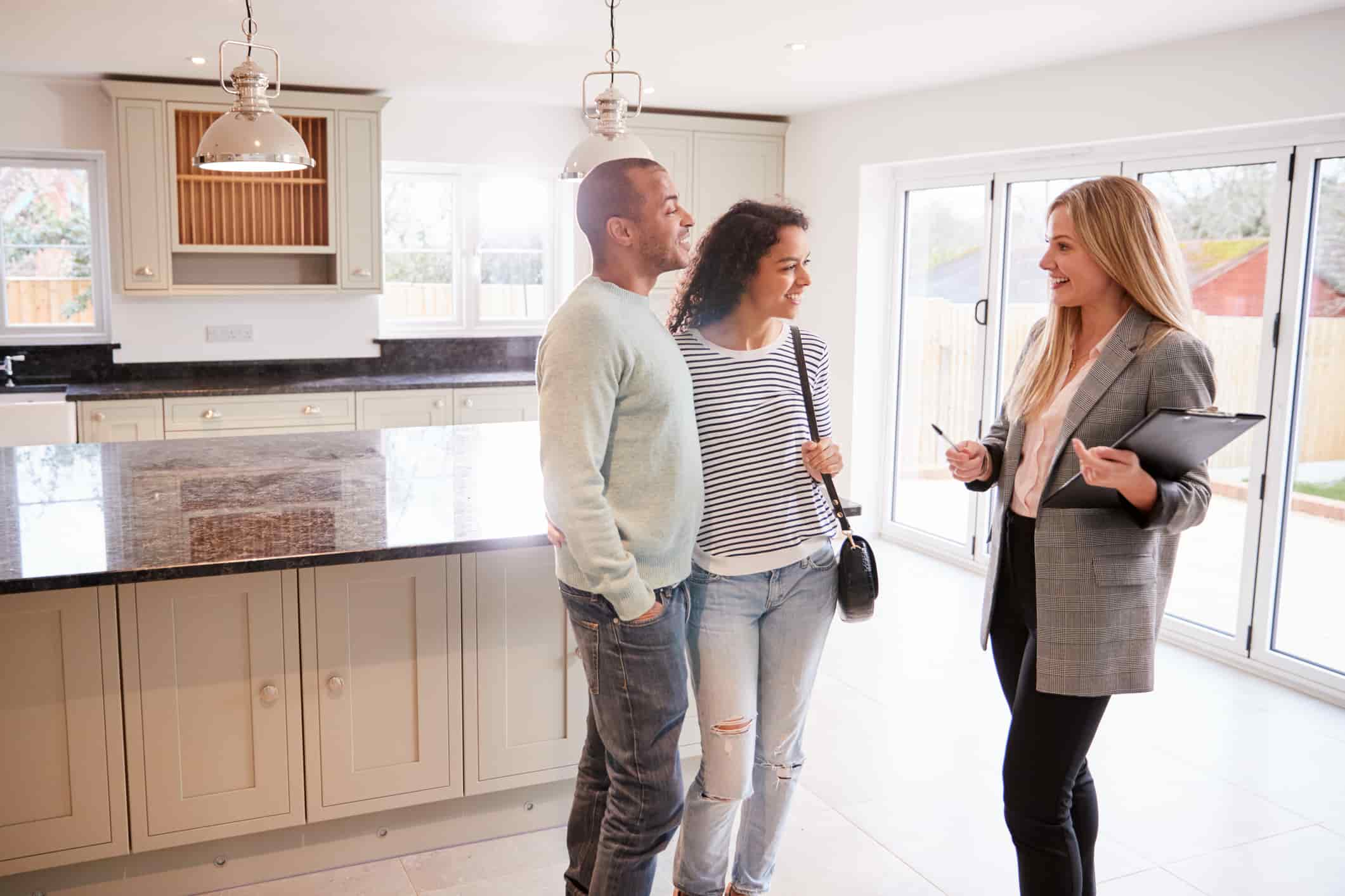 Female realtor showing a house to a couple