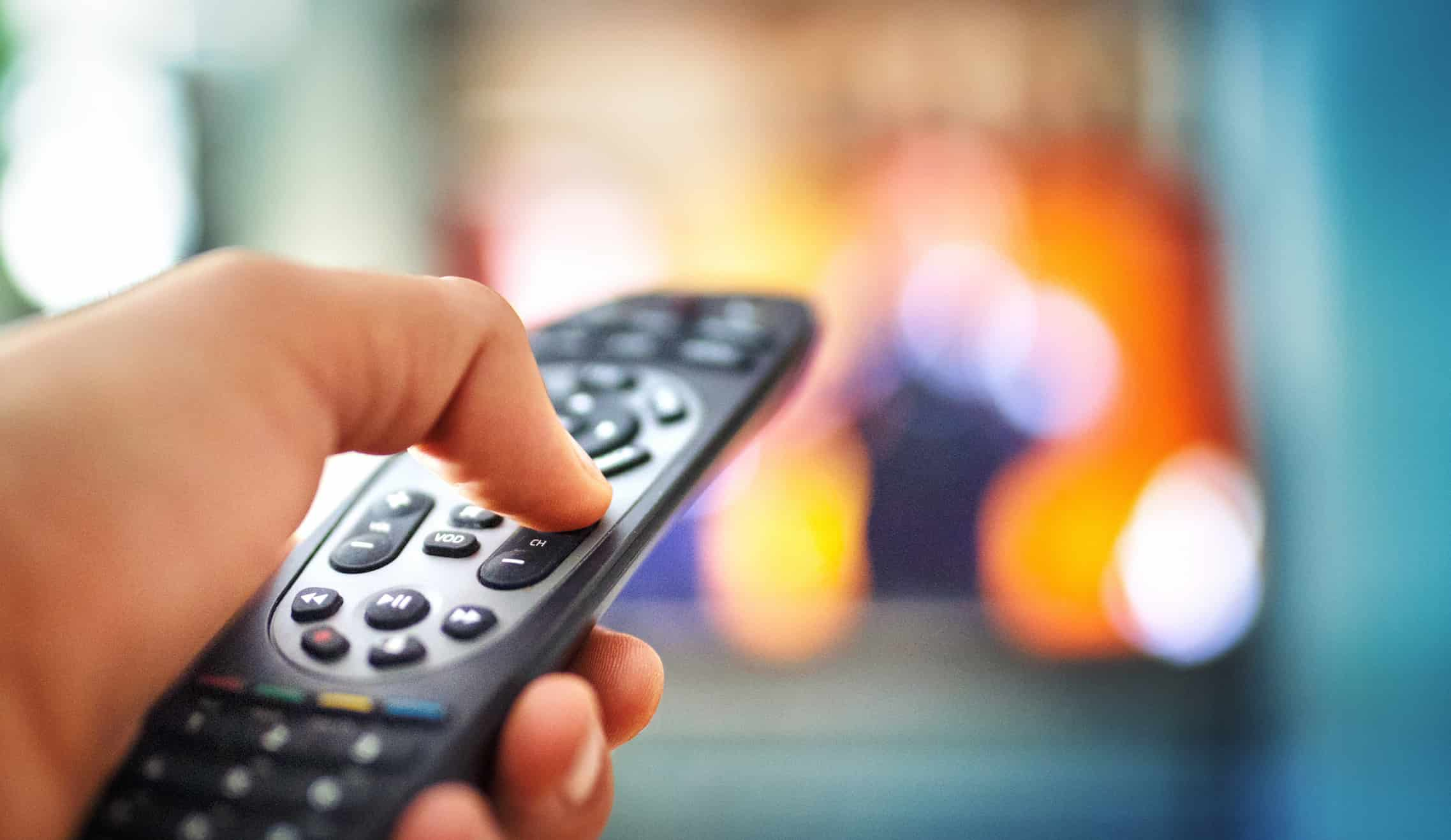 A person holding a TV remote with a blurred TV in the background