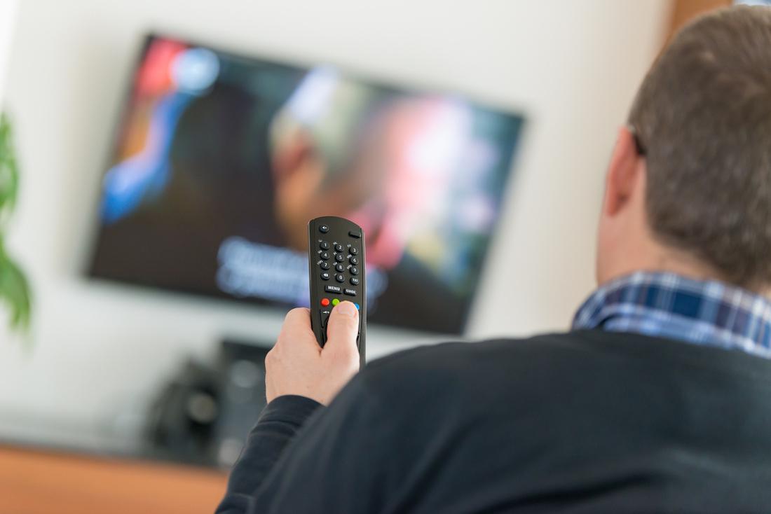 Man using remote while watching tv