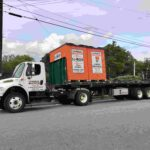 A truck driving with a load of two orange U-Box moving containers