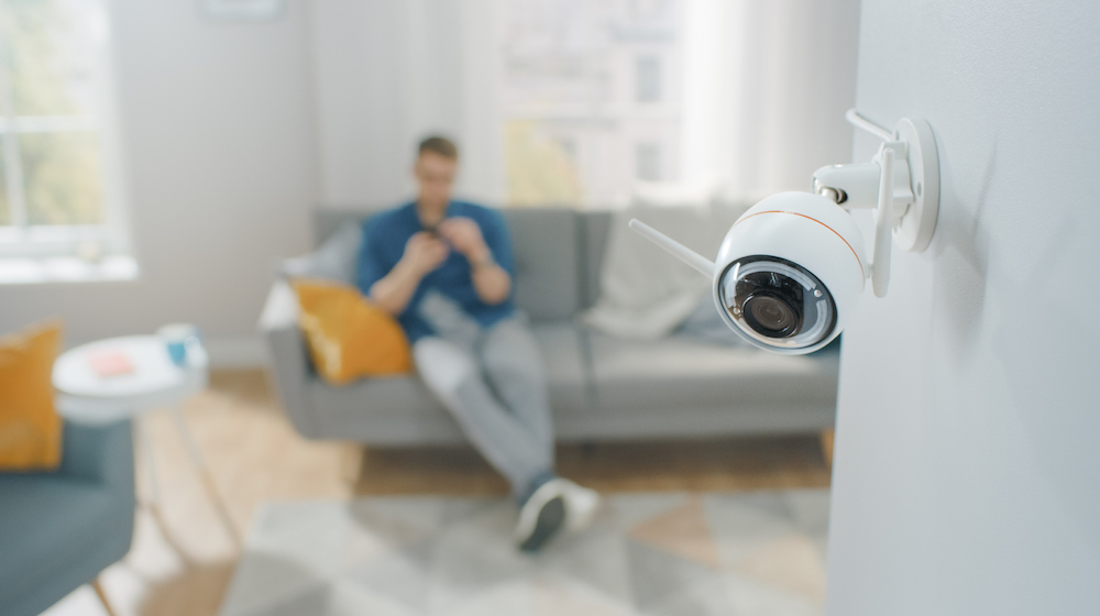 Man sitting in home with security camera