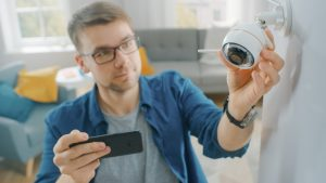 Man setting home security camera