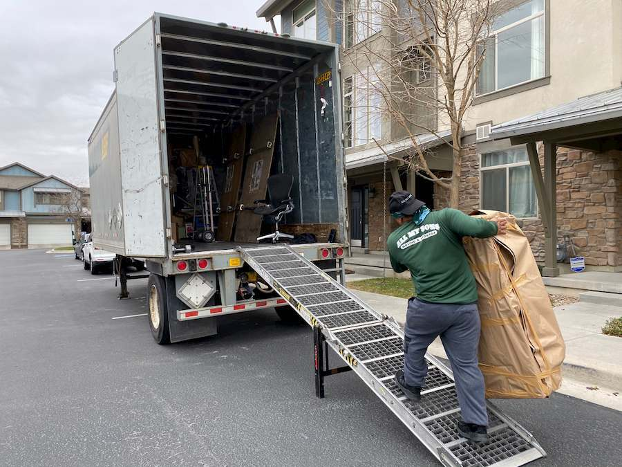 A worker carries a large box up a loading ramp and into a U-Pack trailer