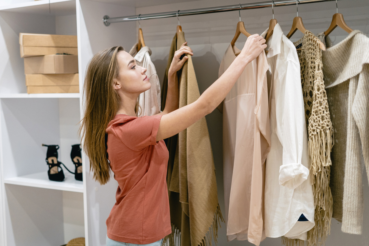Young woman looking at clothes in her closet